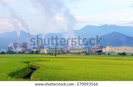 Factory in the middle of a green Farmland on a  cloudy day~ - stock photo