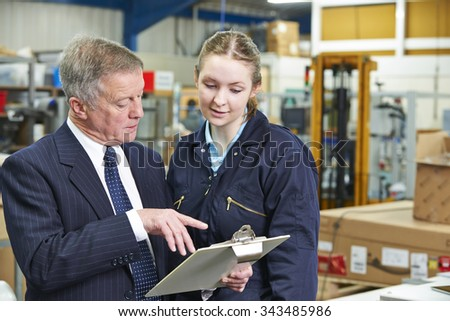 Factory Manager And Apprentice Engineer Looking At Clipboard