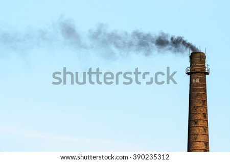 Factory pipe coming from it and black smoke. - stock photo