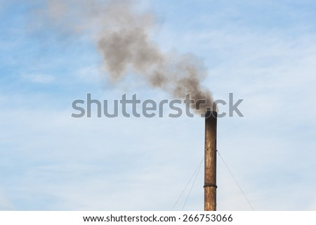 Factory plant with balck smoke and blue sky