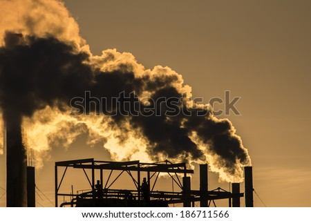 Factory smoke pollution environment on sunset  - stock photo