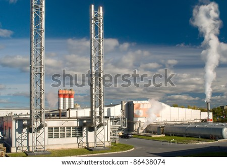 Factory with a chimney and smoke - stock photo