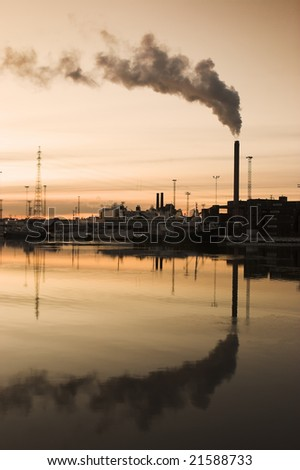 Factory with smoking chimney in sea shore - stock photo