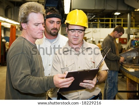 Factory worker and foreman discuss inspection report with auditor. - stock photo