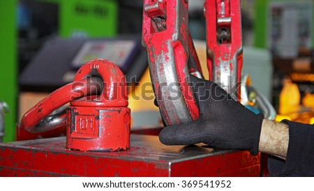 Factory Worker Attaching Crane Hooks to a Heavy Load. Heavy load being hooked with metal hooks of an overhead crane to be transported inside the factory hall. - stock photo