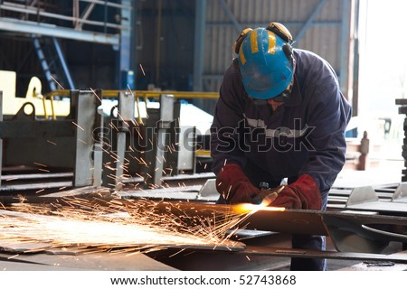 Factory worker cutting metal using acetylene torch - stock photo