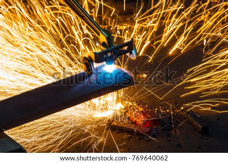 Factory worker cutting metal using acetylene torch, manual plasma cuting in a steel factory lot's of sparks all over