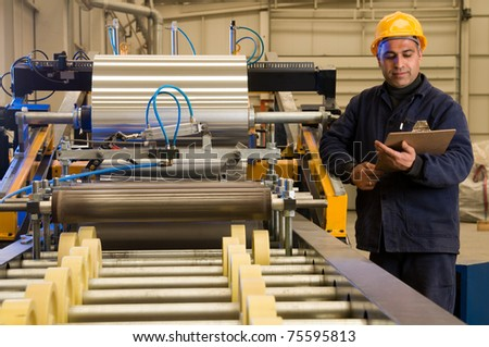 Factory worker processing roll of steel sheet - a series of METAL INDUSTRY images. - stock photo