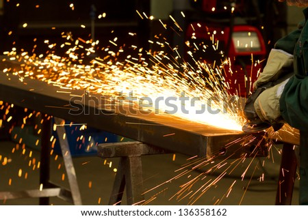 factory worker using electric grinder - stock photo