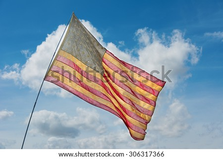 Faded American flag flying against a blue sky - stock photo