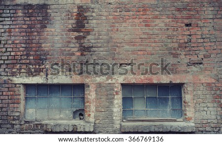 Faded industrial brick building wall with blue windows.