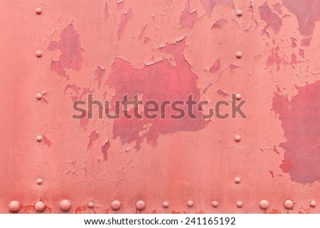 Faded pink paint with red underneath on steel metal with cracks, chips, splits, and paint bubbles with large and small rivet screws. - stock photo
