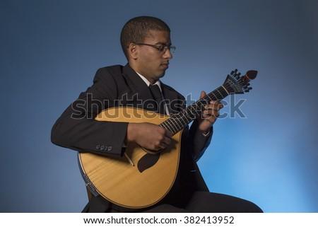 fado musician with a portuguese guitar, studio - stock photo