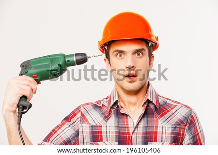 Fail. Shocked young handyman in hardhat aiming his head with drill and looking at camera while standing against grey background - stock photo