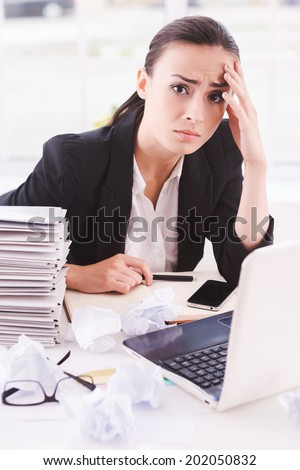 Failed again. Frustrated young woman in formalwear looking at camera while sitting at her working place - stock photo