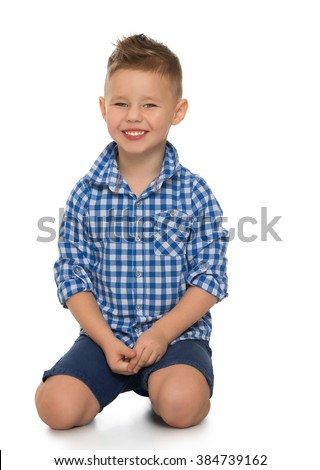 Fair-haired little boy in blue in a plaid shirt and blue shorts is kneeling on the floor.close-up - Isolated on white background - stock photo