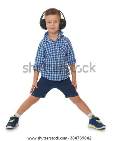 Fair-haired little boy in blue in a plaid shirt and blue shorts, listening to big black stereo headphones music - Isolated on white background - stock photo