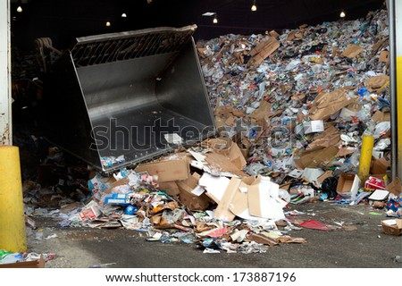 FAIRFAX, VA - DECEMBER 5: Crane moving paper and plastic inside of a recycling facility on December 5, 2013 in Fairfax, VA. The plastic will be separated from the paper on a conveyor belt. - stock photo
