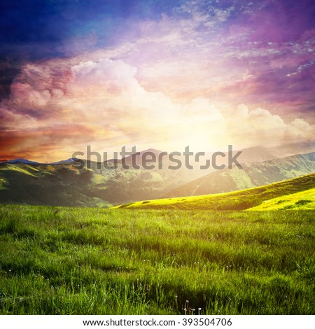 Fairtytale landscape with green grass, mountains, sunset fantastic sky. Summer adventure - stock photo