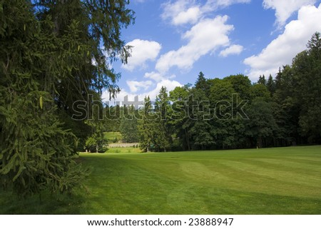 fairway of a beautiful golf course with dramatic summer sky - stock photo