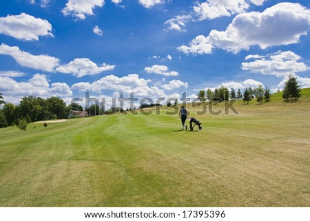 fairway of a beautiful golf course with golfer under dramatic summer sky - stock photo