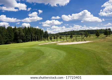 fairway of a beautiful golf course with sand bunkers under dramatic summer sky - stock photo