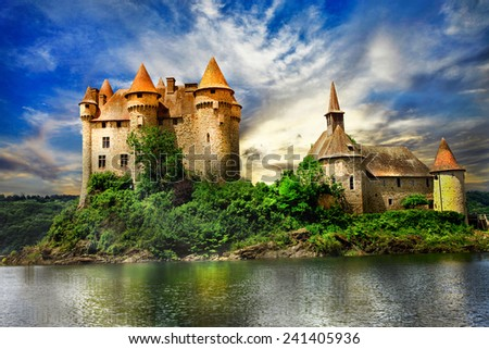 fairy castle on lake over sunset - chateau de Val, France - stock photo
