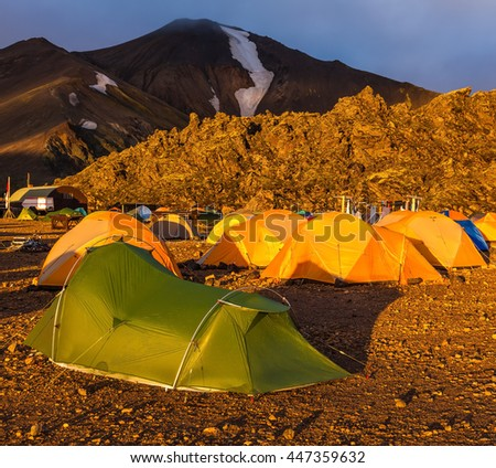 Fairy dawn National Park Landmannalaugar, Iceland. Tents tourists, mountains and glaciers covered with warm sunlight