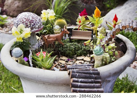 Fairy garden with deer, gazing balls and mushrooms in a flower pot - stock photo
