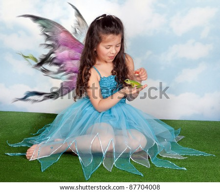 Fairy girl putting a golden crown on a frog prince charming - stock photo