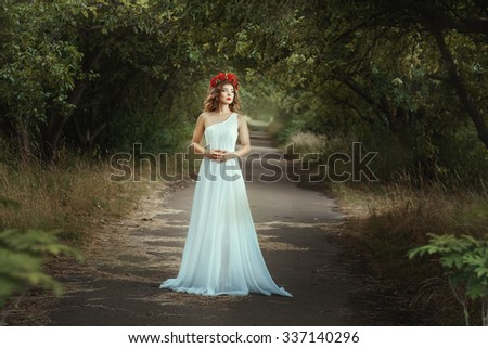 Fairy girl standing on the road in  woods.  She lightweight white dress and red wreath on his head with long hair. - stock photo
