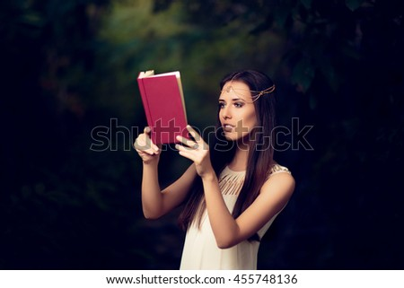 Fairy Princess Girl Reading Story Book - Magic portrait of fairytale goddess woman in nature  - stock photo