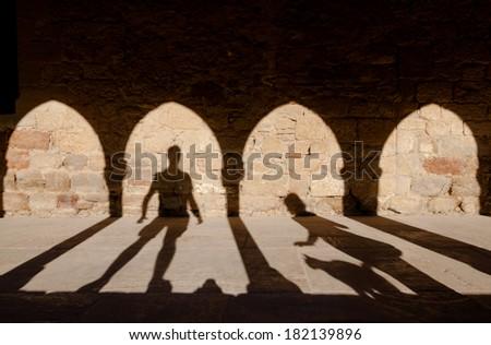 Fairy tail man girl and cat shadows under arcade - stock photo
