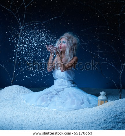 Fairy Tale - portrait of beautiful frozen fairy nymph girl sitting on snow and blowing snowflakes from her hands - stock photo