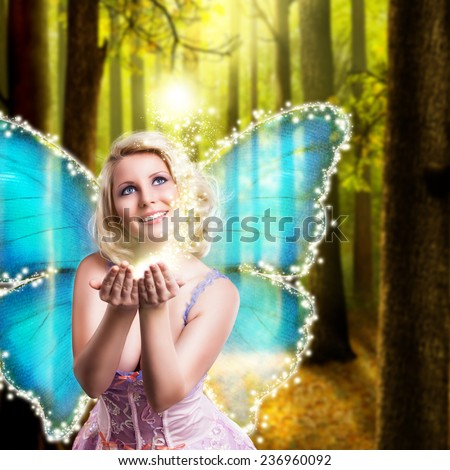 fairy with some magic in front of an enchanted forest - stock photo