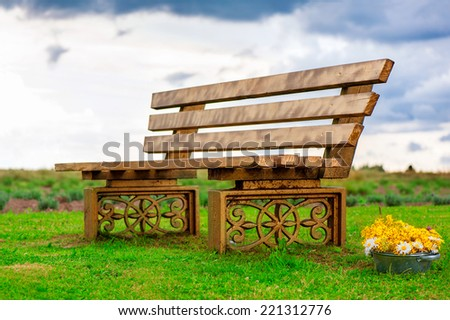 Fairytale ancient bench on bright dramatic cloudy sky background. Outdoors. - stock photo