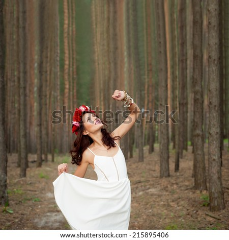 Fairytale in the forest. Beautiful  woman wearing white dress and with red roses hairband in pine forest. - stock photo