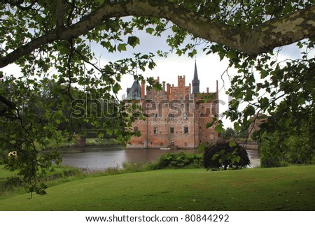 Fairytale like medieval Egeskov Castle on the island of Funen in Denmark seen through the lush of a tree