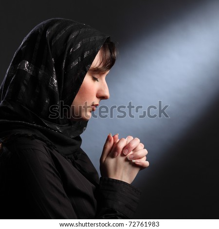 Faith of young religious woman wearing black hijab headscarf, eyes closed and hands together in prayer.