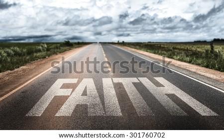 Faith written on rural road - stock photo