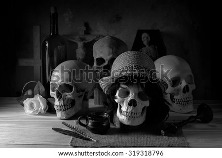 Faithful and sin concept on religion abstract with skull wearing hat and Christian cross in background black and white version - stock photo