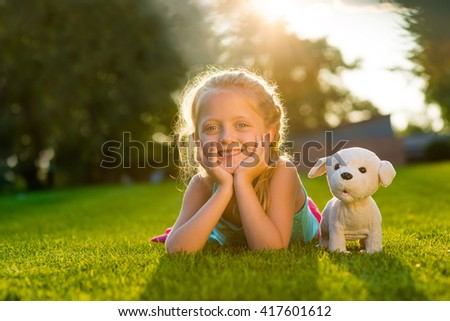 Faithful friends' photo made in park with very green grass and high concentration of sunlight. Cute child's smile. Trees in the background. - stock photo