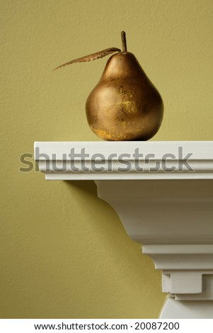 Fake gold colored pear on a mantle