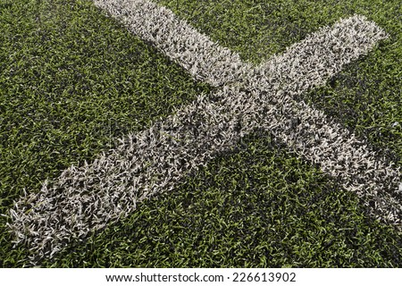 Fake grass soccer field  with cross white lines (textured background) - stock photo