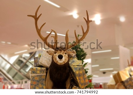 Fake,stuffed reindeer,carrying wrapped present boxes,as the symbol of  Christmas gifting,as decoration in a big store.