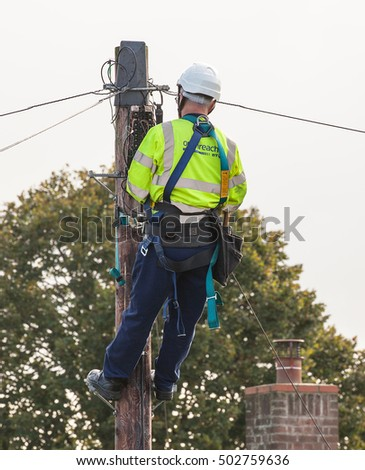 FAKENHAM, NORFOLK / UK - 10th OCTOBER 2016: Openreach BT engineer fixing cables up a pole. UK internet and telephone provider at work providing internet and telephone services to rural locations