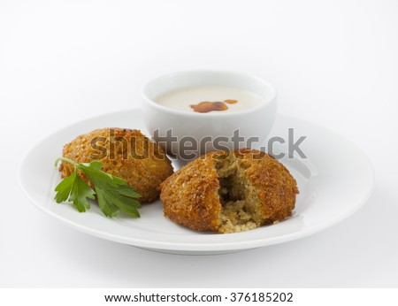 Falafel appetizer with sauce, one falafel is broke open to see the goodness inside. Part of a Greek, Mediterranean or Middle Eastern Diet, - stock photo