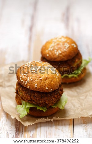 Falafel burger with addition of Iceberg lettuce on a wooden rustic table. Healthy and delicious  vegetarian dish - stock photo