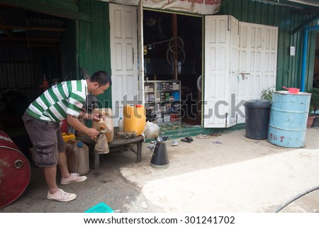 FALAM, MYANMAR - JUNE 17 2015: Refilling petrol in the recently opened to foreigners area of Chin State - western Myanmar (Burma) - stock photo