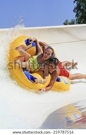 Faliraki,Rhodes, Greece-August 28,2014:Boyfriend and a Girlfriend in a very interesting way drive with tube on the rafting slide in the  Water park.Rafting slide is one of many popular game  in park. - stock photo